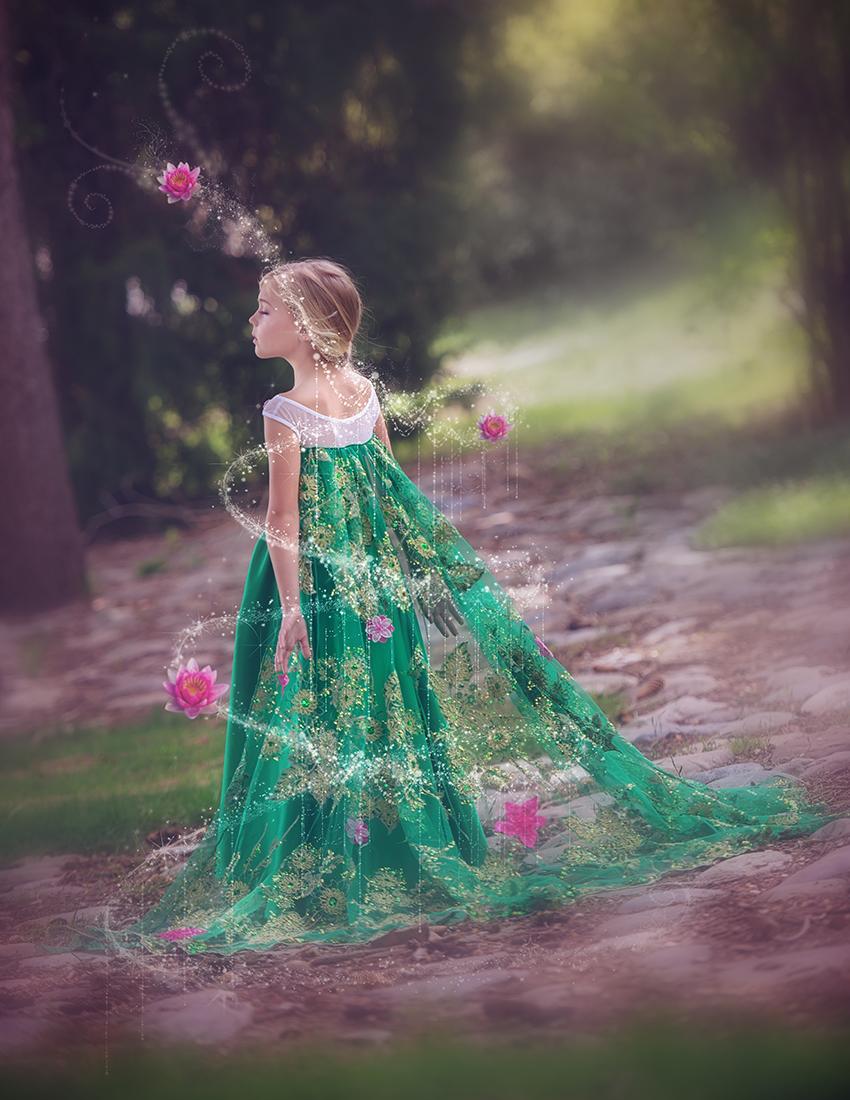 Фото Девочка в длинном платье в окружении цветов на фоне природы