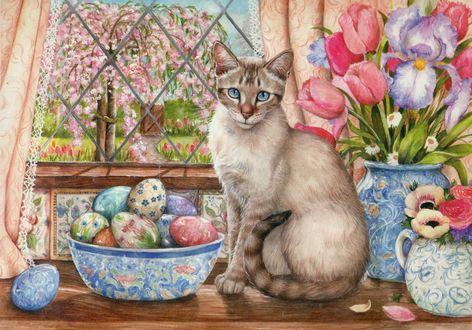 Фото Кошка сидит на столе у окна возле чашки с пасхальными яйцами и ваз с цветами