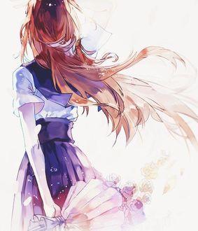 Фото Девушка с длинными волосами, в японской школьной форме, с букетом в руке, стоит к нам спиной