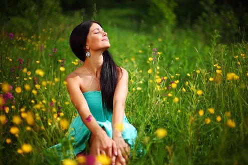 Фото Темноволосая девушка с закрытыми глазами сидит на траве с цветами