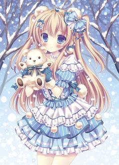 Фото Девушка держит игрушку медвежонка в руках под снегом