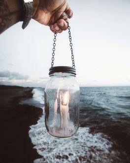 Фото Мужская рука держит банку со свечой над морем