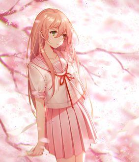 Фото Девушка в школьной форме с конвертом в руке стоит у дерева сакуры
