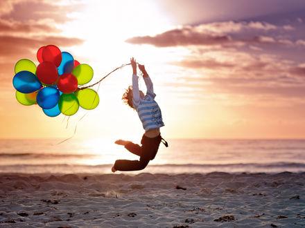 Фото Мальчик с воздушными шариками в руках в прыжке на фоне морского пейзажа, by Angela Lumsden