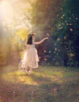 Фото Улыбающаяся девочка в венке из цветов с клеткой в одной руке, другую руку протянула к порхающим бабочкам