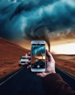 Фото Человек снимает торнадо на камеру телефона