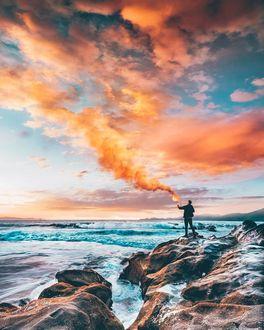 Фото Парень с дымовой шашкой стоит на каменистом берегу моря