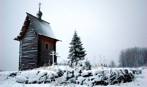Фото Часовня стоит рядом с елкой
