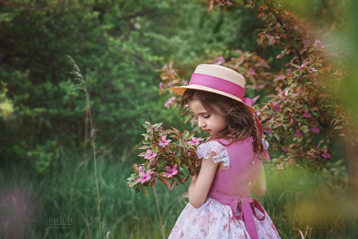 Фото Девочка в шляпке стоит у цветущей ветки дерева. Фотограф Деева Елена