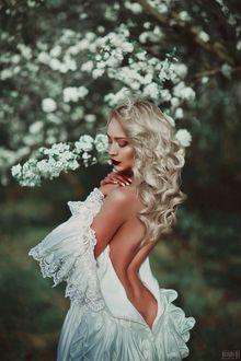 Фото Девушка с оголенной спиной стоит на фоне весеннего цветущего дерева, фотограф Светлана Беляева