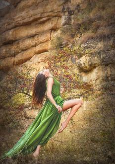 Фото Девушка в длинном зеленном платье стоит на одной ноге запрокинув голову назад у скалы, by Ilona