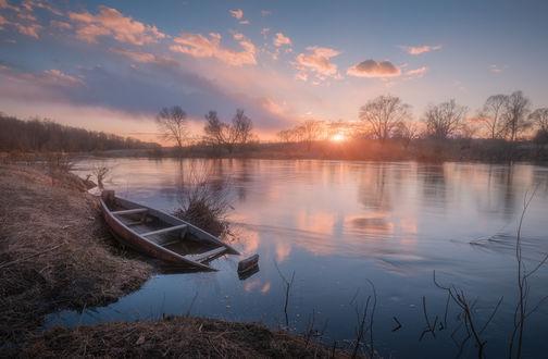 Фото Полузатопленная лодка в реке на заходе солнца
