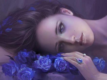 Фото Печальная девушка с пепельными волосами и сиреневыми глазами лежит на синих розах, с лепестками в волосах и кольцами на пальцах