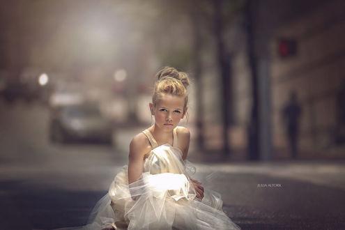 Фото Свеловолосая девочка в кремовом платье сидит на дороге на размытом фоне, by Julia Altork