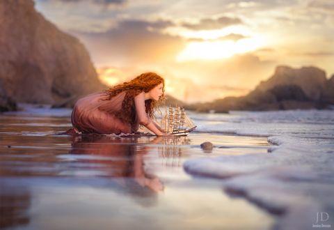 Фото Рыжеволосая девушка с корабликом у колен в воде, by Jessica Drossin