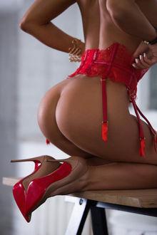 Фото Полуобнаженная девушка сидит на коленях в туфлях и красном поясе для чулок