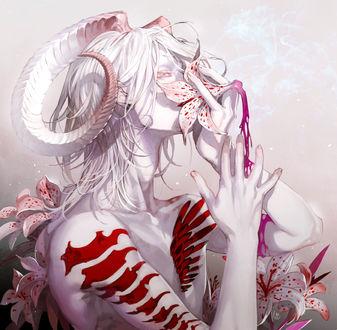Фото Парень с рогами прикладывает к носу цветок магнолии