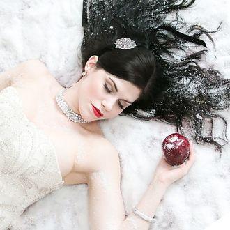 Фото Темноволосая девушка с украшениями, с закрытыми глазами, с яблоком в руке лежит на снегу