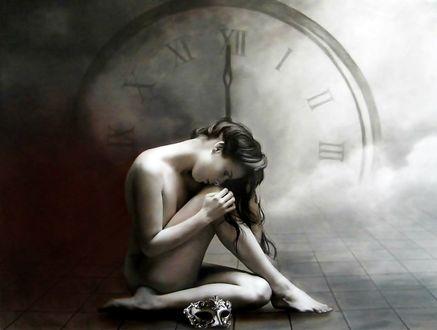 Фото Обнаженная девушка сидит на полу склонив голову к коленям, на фоне часов, рядом с ней лежит маска, by Brita Seifert