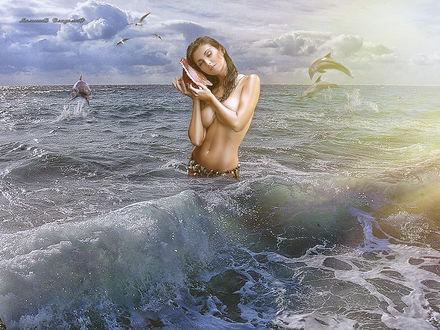 Фото Девушка в море слушает ракушку прижав ее к уху