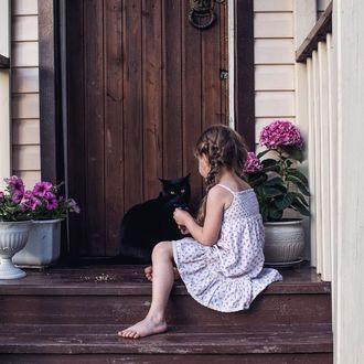 Фото Девочка сидит на ступеньках дома с черной кошкой