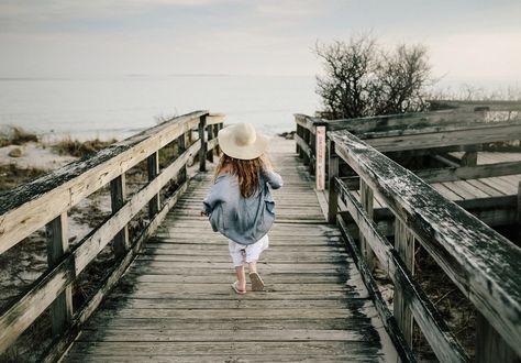 Фото Девочка бежит по деревянному мосту к реке