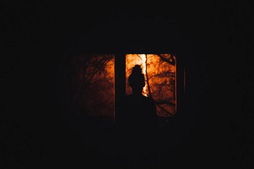 Фото Силуэт девушки в темной комнате, смотрящей в окно на осенний пейзаж, by Rona-Keller