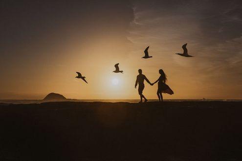 Фото Влюбленные стоят на фоне заката