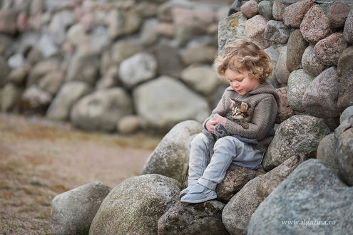 Фото Мальчик со своим котенком сидит на камнях. Фотограф Елена
