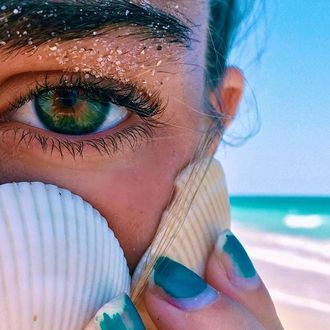 Фото Девушка с ракушкой у лица