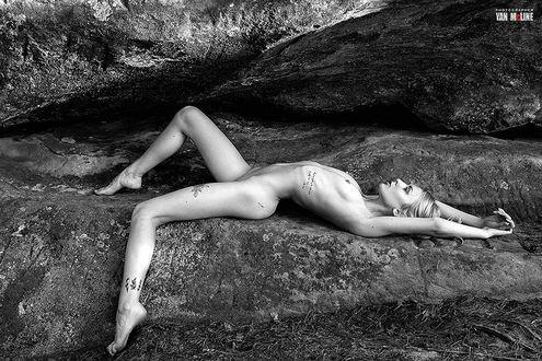 Фото Модель Настя Польна лежит на камнях