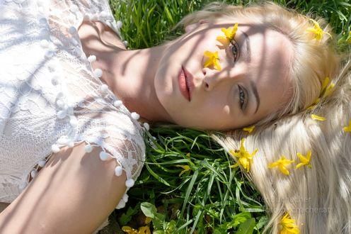 Фото Девушка лежит на зеленой траве с весенними цветочками на ней, фотограф Peter Buchacher