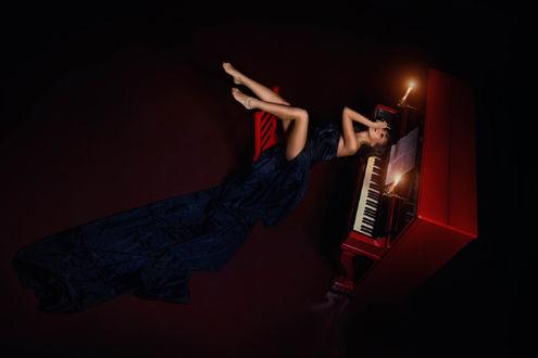 Фото Девушка в длинном синем платье сидит у красного пианино