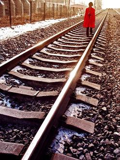 Фото Девушка в красном пальто идет по железной дороге