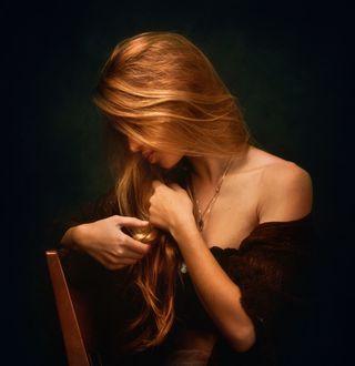 Фото Девушка с длинными волосами сидит на стуле, склонив голову, фотограф Zachar Rise