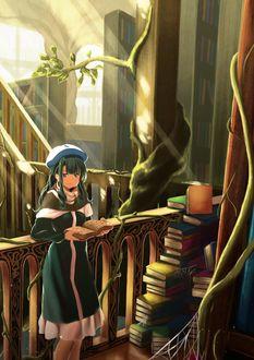 Фото Девочка с книгой в руке стоит у стопки книг