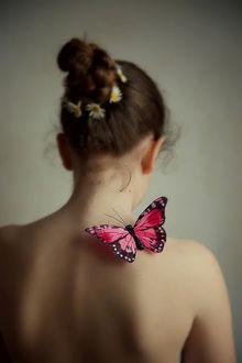 Фото Девушка, с ромашками в волосах и бабочкой на теле, стоит к нам спиной