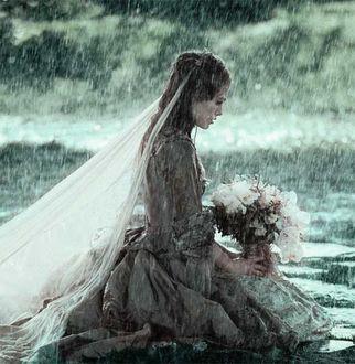 Фото Актриса Keira Christina Knightley / Кира Найтли в роли Элизабет Суонн в свадебном платье с букетом цветов сидит под дождем, фильм Пираты Карибского моря