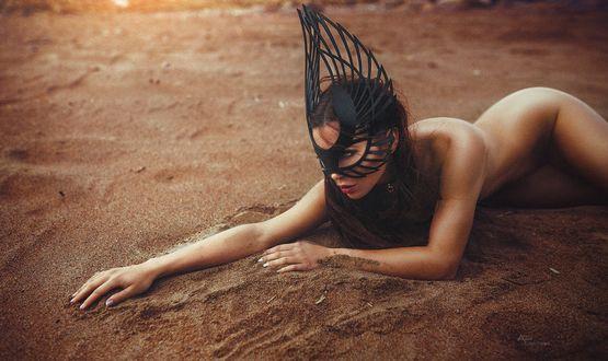 Фото Обнаженная девушка с маской на лице лежит на песке, фотограф Annet Tukacheva