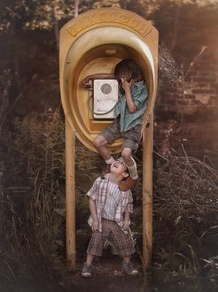 Фото Ребенок, стоя на плечах у друга, звонит с таксофона. Фотограф Надежда Шибина