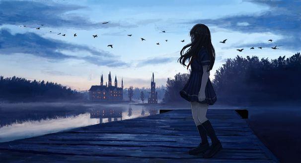 Фото Девушка стоит на мостике и смотрит на водоем