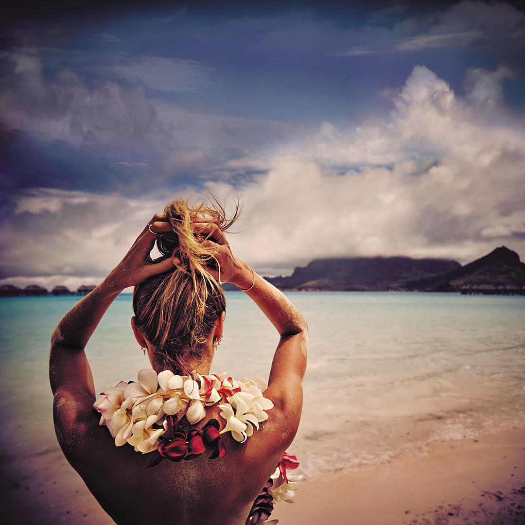 Фото Девушка с цветами вокруг шеи держит руки на голове, сидя на фоне моря