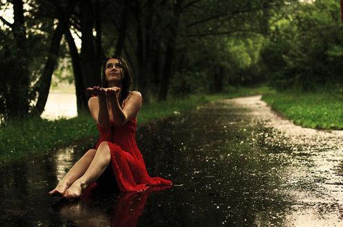 Фото Улыбающаяся босоногая девушка сидит на мокром асфальте, подняв руки перед собой к каплям дождя