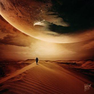 Фото Силуэт мужчины в пустыне, в небе над ним планета