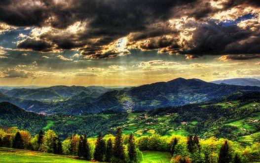 Фото Солнечные лучи сквозь облака падают на зеленые холмы