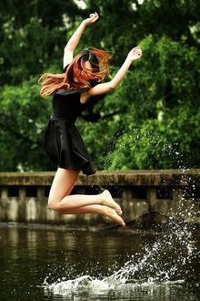 Фото Девушка в черном платье в прыжке над водой, фотограф T T