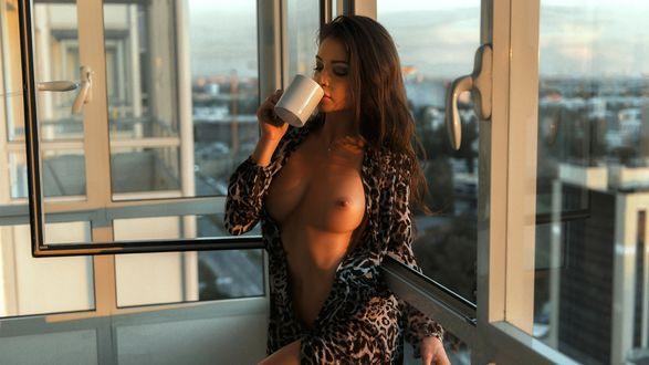 Фото Симпатичная брюнетка с кружкой в руке и в распахнутом халате, оголившем ее грудь, стоит на балконе, на фоне городского пейзажа