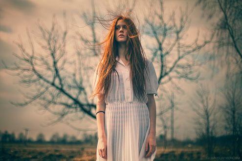 Фото Девушка с развивающимися волосами стоит на фоне унылого пейзажа. Фотограф Jaroslav Monchak