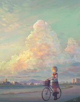 Фото Девочка с велосипедом стоит на дороге на фоне облачного неба