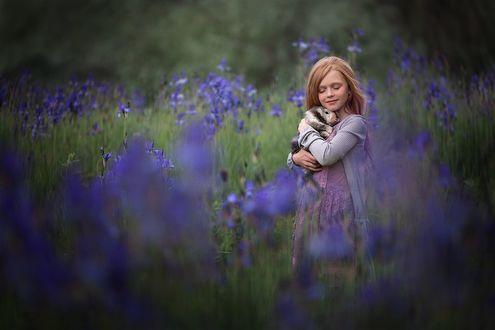 Фото Улыбающаяся девочка с закрытыми глазами прижимает к себе кролика на фоне цветущих ирисов. Фотограф Ольга Ротова